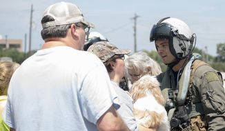 In this Aug. 31, 2017, photo provided by the U.S. Navy, Aircrewman 2nd Class Jansen Schamp, right, speaks with Harvey evacuees while rescuing them from a shelter in Vidor, Texas. (Mass Communication Specialist 1st Class Christopher Lindahl/U.S. Navy via AP)