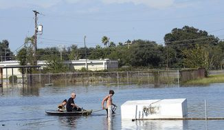 Port Arthur residents traverse a flooded lot along Memorial Blvd. Thursday, Aug. 31, 2017 in Port Arthur, Texas.  (Kim Brent/The Beaumont Enterprise via AP)