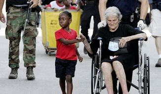 FILE - In this Sept. 3, 2005 file photo, Tanisha Belvin, 5, holds the hand of fellow Hurricane Katrina victim Nita LaGarde, 89, as they are evacuated from the Convention Center in New Orleans, La. Hundreds of people waited several days to be evacuated. (AP Photo/Eric Gay, File)