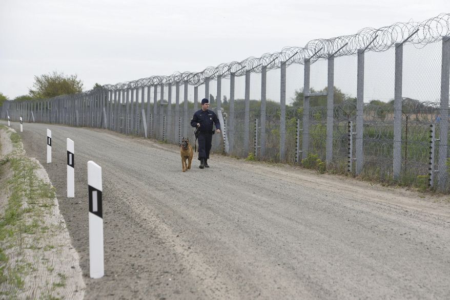 "FILE - In this April 28, 2017 file photo a police officer with a dog patrols along the border fence on the Hungarian-Serbian border near Roszke, 180 kms southeast of Budapest, Hungary. Hungary's prime minister is asking the European Union to pay for half of the costs of anti-migrant fences it built on its southern borders, some 440 million euros ($523 million). In a letter dated Thursday, Aug. 31, 2017 to EU Commission President Jean-Claude Juncker, Prime Minister Viktor Orban says the fences erected in 2015 protect not just Hungary ""but entire Europe"" from ""the flood of illegal migrants."" (Zoltan Gergely Kelemen/MTI via AP, file)"