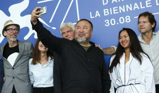 "Artist Ai Weiwei, center, snaps selfie photographs during the photo call for the film ""Human Flow"" at the 74th Venice Film Festival at the Venice Lido, Italy, Friday, Sept. 1, 2017. (Photo by Joel Ryan/Invision/AP)"