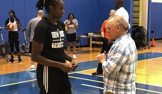 New York Liberty WNBA basketball player Tina Charles talks with Dan Carlson after practice at the team training center in Greenburgh, N.Y., Friday, Sept. 1, 2017. One of the hundreds of defibrillators that Charles has donated over the past four years wound up saving Carlson's life when he had a heart attack in July. (AP Photo/Doug Feinberg)