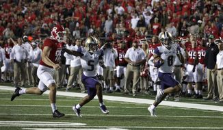Washington wide receiver Dante Pettis (8) runs a punt-return for a touchdown as as Andre Baccellia (5) blocks Rutgers punter Ryan Anderson during the first half of an NCAA college football game Friday, Sept. 1, 2017, in Piscataway, N.J. (AP Photo/Mel Evans)