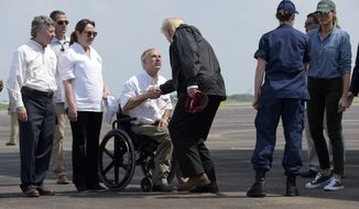 President Donald Trump shakes hands with Texas Gov. Greg Abbott as he and first lady Melania Trump, right, arrive via Air Force One at Ellington Field in Houston, Saturday, Sept. 2, 2017. The president and first lady Melania Trump arrived Saturday morning in Houston, and their first order of business is to meet with people impacted by the storm and flooding. Theyre also set to stop by a relief center to speak with volunteers and then head to Lake Charles, Louisiana, another area devastated by Harvey.   (AP Photo/Susan Walsh)