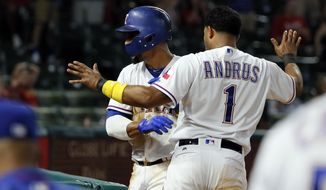 Texas Rangers' Carlos Gomez, rear, and Elvis Andrus (1) celebrate after Gomez scored on a wild pitch by Los Angeles Angels relief pitcher Cam Bedrosian during the eighth inning of a baseball game, Friday, Sept. 1, 2017, in Arlington, Texas. (AP Photo/Tony Gutierrez)