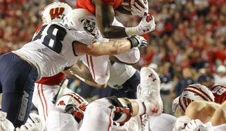 Wisconsin running back Bradrick Shaw (7) scores against Utah State's Chase Christiansen (48) during the first half of an NCAA college football game Friday, Sept. 1, 2017, in Madison, Wis. (AP Photo/Andy Manis)