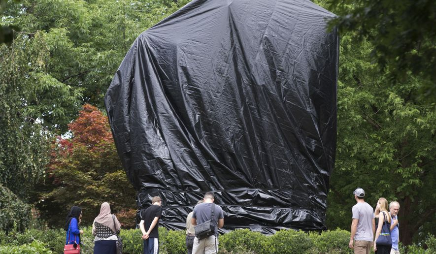 FILE - In this Wednesday, Aug. 23, 2017 file photo, people look at the covered statue of Confederate Gen. Robert E. Lee in Emancipation Park in Charlottesville, Va. The move to cover the statues was intended to symbolize the city's mourning for Heather Heyer, killed while protesting a white nationalist rally earlier in the month. (AP Photo/Steve Helber)