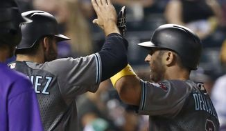 Arizona Diamondback' Daniel Descalso, right, celebrates a three-run home run with teammates during the seventh inning of a baseball game against the Colorado Rockies on Friday, Sept. 1, 2017, in Denver. (AP Photo/Jack Dempsey)