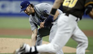Los Angeles Dodgers starting pitcher Clayton Kershaw, left, fields a ground ball to throw out San Diego Padres' Carlos Asuaje during the first inning of a baseball game in San Diego, Friday, Sept. 1, 2017. (AP Photo/Alex Gallardo)