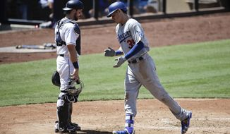 Los Angeles Dodgers' Cody Bellinger, right, celebrates his home run as he heads to the dugout past San Diego Padres catcher Austin Hedges during the fourth inning of a baseball game, Saturday, Sept. 2, 2017, in San Diego. (AP Photo/Jae C. Hong)