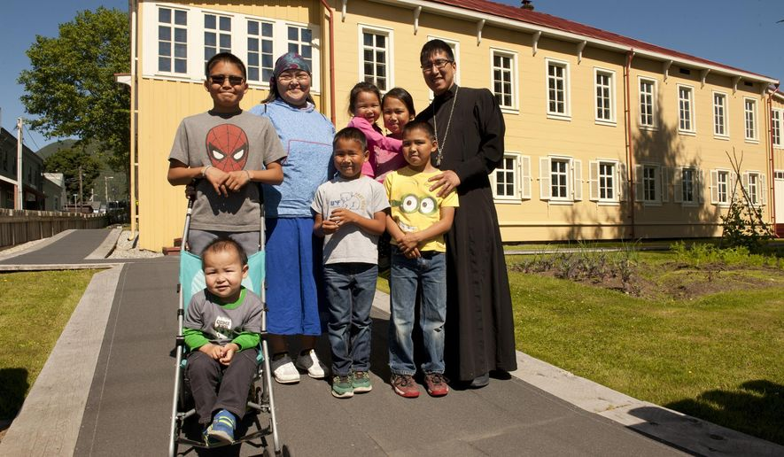 In an Aug. 4, 2017 photo, Father Ishmael Andrew, right, the new priest at St. Michael's Orthodox Cathedral, and his family pose outside the Russian Bishop's House in Sitka, Alaska. Pictured are from left, Elijah (Elgin), Theophan (in stroller), Matushka Anastasia, Cyril, Yakova (Odessa), Senaida, Aidan and Father Andrew. The family has been in Sitka since August 2, 2017, arriving from Napaskiak, where they lived for the last seven years. (James Poulson/Daily Sitka Sentienl via AP)
