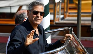 Actor George Clooney waves to photographers as he arrives on a motorboat during the 74th edition of the Venice Film Festival, in Venice, Italy, Saturday, Sept. 2, 2017. (Ettore Ferrari/ANSA via AP)