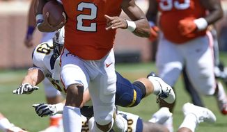 Clemson quarterback Kelly Bryant outruns Kent State defenders Matt Bahr (29) and Dominic Hill (98) to gain a first down during the first half of an NCAA college football game Saturday, Sept. 2, 2017, in Clemson, S.C. (AP Photo/Richard Shiro)