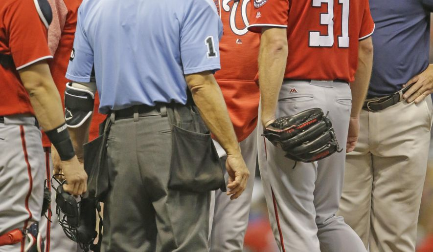 Washington Nationals manager Dusty Baker, center, visits pitcher Max Scherzer (31) during the fourth inning of a baseball game against the Milwaukee Brewers Saturday, Sept. 2, 2017, in Milwaukee. (AP Photo/Jeffrey Phelps)
