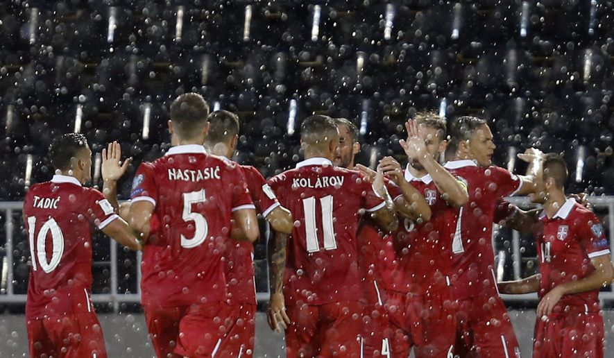 Serbia's Mijat Gacinovic, obscured, celebrates with his teammates after scoring the first goal of his team during the World Cup Group D qualifying soccer match between Serbia and Moldova at the Partizan Stadium in Belgrade, Serbia, Saturday Sept. 2, 2017. (AP Photo/Darko Vojinovic)