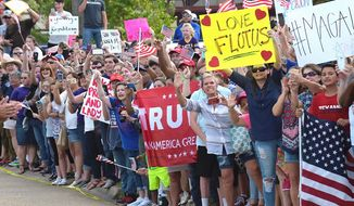 People hold signs near the National Guard Armory in Lake Charles, La., where President Donald Trump and first lady Melania Trump are meeting with members of the county emergency operations center and Cajun Navy for those impacted by Hurricane Harvey, Saturday, Sept. 2, 2017. (AP Photo/Susan Walsh) (credit)