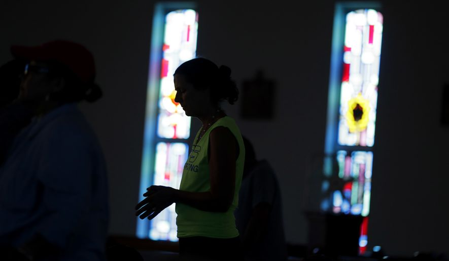 Caren Chiders attends Mass at St. Joseph Catholic Church which was damaged from the effects of Hurricane Harvey, Sunday, Sept. 3, 2017, in Port Aransas, Texas. The church and Port Aransas is still without electricity. (AP Photo/Eric Gay)