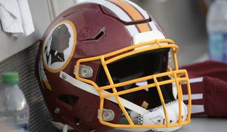 A Washington Redskins helmet sits on a bench during the singing of the national anthem before an NFL preseason football game against the Tampa Bay Buccaneers Thursday, Aug. 31, 2017, in Tampa, Fla. (AP Photo/Phelan M. Ebenhack)