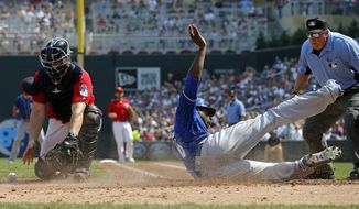 Kansas City Royals' Lorenzo Cain, center, scores past Minnesota Twins catcher Chris Gimenez, left, who cannot handle the throw to the plate in the fourth inning of a baseball game Sunday, Sept, 3, 2017, in Minneapolis. (AP Photo/Jim Mone)