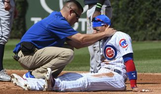 Chicago Cubs second baseman Javier Baez (9) is helped by a member of the Chicago Cubs staff after he was injured during a play against the Atlanta Braves during the second inning of a baseball game on Sunday, Sept. 3, 2017, in Chicago. (AP Photo/Matt Marton)