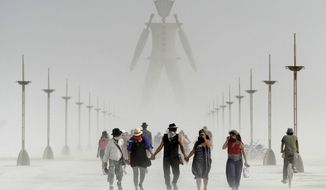 In this Aug. 29, 2014, file photo, Burning Man participants walk through dust at the annual Burning Man event on the Black Rock Desert of Gerlach, Nev. A Nevada sheriff says a man who ran into the flames at the Burning Man festival's signature burning ceremony has died. Pershing County Sheriff Jerry Allen identified the man as Aaron Joel Mitchell, 41, who died Sunday, Sept. 3, 2017, morning at the UC Davis hospital burn center in California. (Andy Barron/The Reno Gazette-Journal via AP, File)