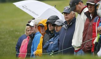 Spectators watch in the rain on the second fairway during the third round of the Dell Technologies Championship golf tournament at TPC Boston in Norton, Mass., Sunday, Sept. 3, 2017. (AP Photo/Michael Dwyer)