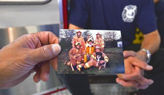In this Aug. 21, 2017, photo, Kevin Miller holds up a photograph depicting three generations of the Herndon and Miller family that currently serve on the Lewis and Clark Fire Department near Warrenton, Ore.  (Colin Murphey/Daily Astorian via AP)