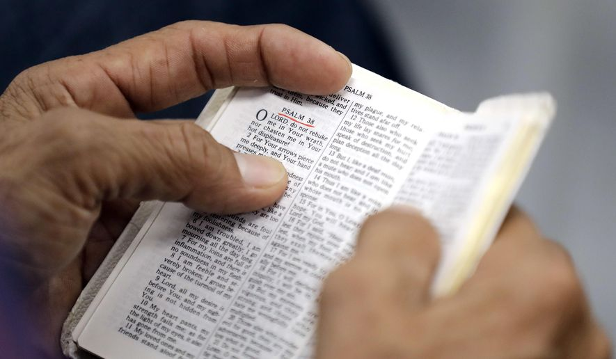 A man holds a Bible during while attending church services in Cypress, Texas. (Associated Press) **FILE**