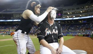 Wearing a monkey mask, Miami Marlins' Miguel Rojas hits relief pitcher Drew Steckenrider with a cream pie during an interview after the Marlins defeated the Philadelphia Phillies 10-9 in a baseball game, Saturday, Sept. 2, 2017, in Miami. (AP Photo/Wilfredo Lee)