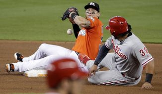 Philadelphia Phillies' Jorge Alfaro (38) is out at second as Miami Marlins third baseman Derek Dietrich loses the ball before throwing to first during the fifth inning of a baseball game, Sunday, Sept. 3, 2017, in Miami. (AP Photo/Lynne Sladky)
