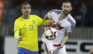 Sweden's Christoffer Nyman, left, struggles for the ball with Belarus' Mikhail Sivakov during the World Cup Group A qualifying soccer match between Belarus and Sweden at the Borisov-Arena stadium, in Borisov, Belarus, Sunday, Sept. 3, 2017. (AP Photo/Sergei Grits)