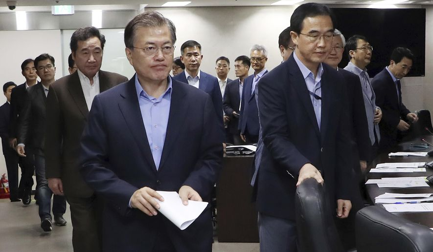 South Korean President Moon Jae-in, left, arrives to presides over a meeting of the National Security Council at the presidential Blue House in Seoul, South Korea, Sunday, Sept. 3, 2017. North Korea said it set off a hydrogen bomb Sunday in its sixth nuclear test, which judging by the earthquake it set off appeared to be its most powerful explosion yet. (Yonhap via AP)