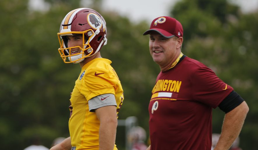 FILE - This July 28, 2017 file photo shows Washington Redskins quarterback Kirk Cousins (8) and head coach Jay Gruen, right, watching during practice at NFL football training camp in Richmond, Va. After a crazy offseason that included firing their general manager and losing their top two receivers, the Redskins should still be playoff contenders in an uncertain NFC East. Playing on the franchise tag for a second consecutive season,  Cousins is playing for another contract, and the defense has been upgraded. All that has Washington thinking about a return to the postseason. (AP Photo/Steve Helber, file)