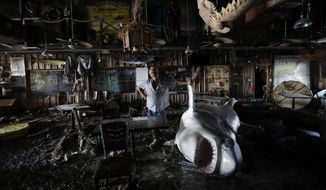 """In this Aug. 30, 2017, photo, Ed Ziegler, owner of Moby Dick's restaurant, surveys the damages to his property after Hurricane Harvey made landfall, in Port Aransas, Texas. """"I made a deal with the Lord that if I survived I'd give him 100 percent. Now I'm hoping he'll settle for 10,"""" he said, using humor to cope with the destruction around him. (AP Photo/Eric Gay)"""