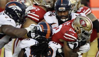 FILE - In this Aug. 19, 2017, file photo, San Francisco 49ers running back Carlos Hyde, right, is tackled by Denver Broncos' Domata Peko (94), top right, Vontarrius Dora, bottom, and Zach Kerr, left, during the first half of a preseason NFL football game, in Santa Clara, Calif. The Broncos begin their season on Sept. 10 against the Los Angeles Chargers. (AP Photo/Eric Risberg, File)