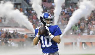 FILE - In this Aug. 21, 2017, file photo, New York Giants quarterback Eli Manning warms up before an NFL preseason football game against the Cleveland Browns,  in Cleveland. The Giants play their first game of the season on Sept. 10 at Dallas. (AP Photo/David Richard, File)