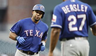 Texas Rangers' Elvis Andrus, left, rounds the bases to high-five third base coach Tony Beasley after hitting a home run in the first inning of a baseball game against the Atlanta Braves in Atlanta, Monday, Sept. 4, 2017. (AP Photo/David Goldman)