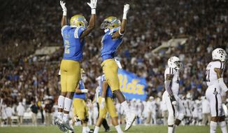 UCLA wide receiver Theo Howard, right, celebrates scoring a touchdown with UCLA wide receiver Jordan Lasley, left, late in the fourth quarter against Texas A&M in an NCAA college football game, Sunday, Sept. 3, 2017, in Pasadena, Calif. UCLA won 45-44. (AP Photo/Danny Moloshok)