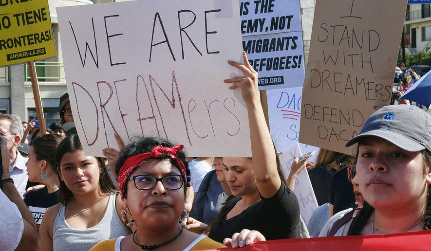 Supporters of the Deferred Action for Childhood Arrivals, or DACA chant slogans and hold signs while joining a Labor Day rally in downtown Los Angeles on Monday, Sept. 4, 2017. President Donald Trump is expected to announce this week that he will end the Deferred Action for Childhood Arrivals, but with a six-month delay, according to two people familiar with the decision-making. (AP Photo/Richard Vogel)