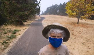 With a precautionary face mask protecting her from the smoky air, Kathleen Soza pays a visit to Skinner Butte Park in Eugene, Ore. with family and friends Monday Sept. 4, 2017, as smoke from nearby wildfires cause health concerns for area residents. (Chris Pietsch/The Register-Guard via AP)