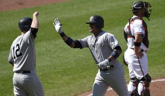 New York Yankees' Starlin Castro, center, celebrates his two-run home run with Chase Headley (12) during the fifth inning of a baseball game as Baltimore Orioles catcher Welington Castillo looks on at right, Monday, Sept. 4, 2017, in Baltimore. (AP Photo/Nick Wass)