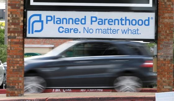 Traffic passes a Planned Parenthood sign in Dallas on June 27, 2016. (Associated Press) **FILE**