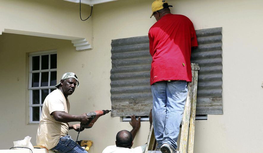 People put up a steel sheet over a window in preparation for Hurricane Irma, in Fort Road, St. John's, Antigua and Barbuda, Tuesday, Sept. 5, 2017.  Irma grew into a dangerous Category 5 storm, the most powerful seen in the Atlantic in over a decade, and roared toward islands in the northeast Caribbean Tuesday on a path that could eventually take it to the United States. (AP Photo/Johnny Jno-Baptiste)