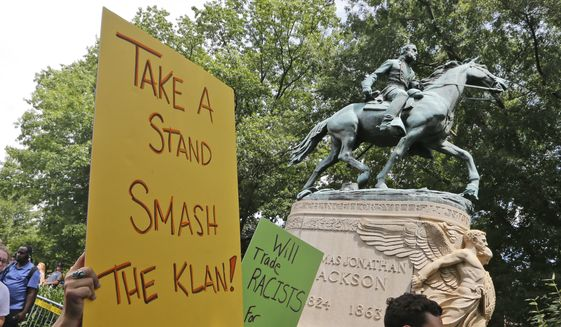 "In this July 8, 2017, file photo, protesters carry signs in front of a statue of Confederate Gen. Thomas ""Stonewall"" Jackson as they demonstrate against a KKK rally in Justice Park in Charlottesville, Va. (AP Photo/Steve Helber, File)"