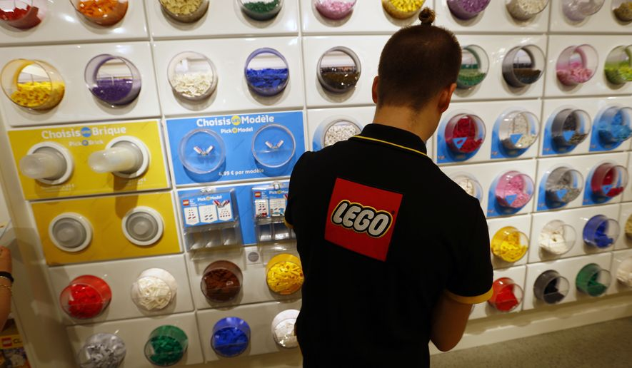 FILE- In this Tuesday, April 5, 2016 file photo, an employee sorts Legos in the the new LEGO flagship store unveiled as part of the new Les Halles shopping mall during the press visit in Paris. Danish toy maker Lego said Tuesday, Sept. 5, 2017, it will cut 1,400 jobs, or about eight percent of its global workforce, after reporting a decline in sales and profits in the first half of 2017. (AP Photo/Francois Mori, File)
