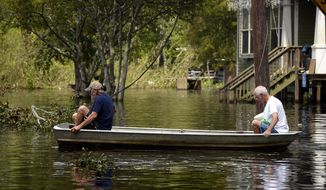 Pete Lawrence, left, and his neighbor, Walton Young, paddle a jon boat through floodwaters at the corner of Fleet Street and Travis Avenue in Orange, Texas, Tuesday, Sept. 5, 2017. (Ryan Pelham/The Beaumont Enterprise via AP)