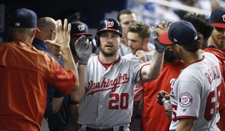 Washington Nationals' Daniel Murphy (20) is congratulated by teammates after he hit a home run during the eighth inning of a baseball game against the Miami Marlins, Tuesday, Sept. 5, 2017, in Miami. The Nationals defeated the Marlins 2-1. (AP Photo/Wilfredo Lee)