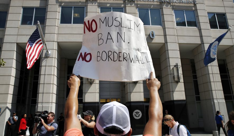 "Jose Quinones, 22, of the Staten Island, borough of New York, holds up a sign saying ""No Muslim Ban. No Border Wall"" as people protest in support of the Deferred Action for Childhood Arrivals (DACA), outside of Immigration and Customs Enforcement in Washington, Tuesday, Sept. 5, 2017. President Donald Trump plans to phase out the DACA program that has protected hundreds of thousands of young immigrants brought into the country illegally as children and call for Congress to find a legislative solution. (AP Photo/Jacquelyn Martin)"