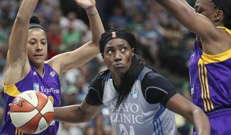 FILE - In this July 6, 2017, file photo, Minnesota Lynx center Sylvia Fowles drives between Los Angeles Sparks players, including Candace Parker, left, during the second half of a WNBA basketball game, in St. Paul, Minn. Fowles had a stellar year to lead Minnesota to the top seed in the WNBA playoffs. Her efforts earned her Associated Press WNBA Player of the Year honors on Tuesday, Sept. 5, 2017. (Elizabeth Flores/Star Tribune via AP, File)