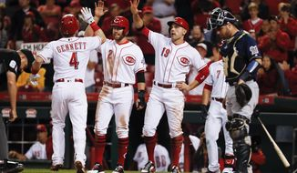 Cincinnati Reds' Scooter Gennett (4) celebrates with Zack Cozart (2) and Joey Votto (19) after hitting a three-run home run off Milwaukee Brewers relief pitcher Wei-Chung Wang during the seventh inning of a baseball game, Tuesday, Sept. 5, 2017, in Cincinnati. (AP Photo/John Minchillo)